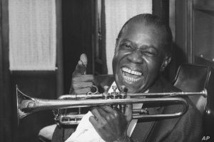 Jazz trumpeter Louis Armstrong, who nearly died this spring, is happily back practicing for his eventual return to work, shown in the upstairs den of his Corona, New York home on June 23, 1971. Armstrong had newsmen in to show his recovery from his near-fatal illness and to thank his fans for their mail during his 10 week hospital stay. (AP Photo/John Rooney)